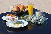 Traditional Israeli Breakfast with two fried eggs, cheeses, salad, fresh rolls, orange juice and a cup of cappuccino served on the Mediterranean Shore