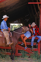 cowboy on a horse talking with two friends sitting on a fence at a ranch in New Mexico