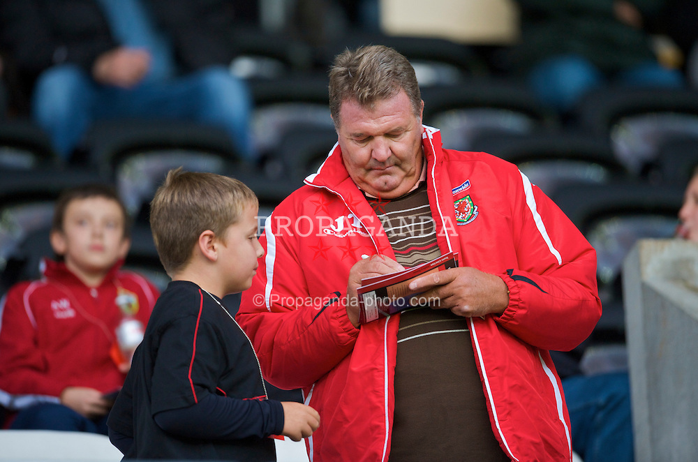SWANSEA, ENGLAND - Friday, September 4, 2009: Wales' manager John Toshack MBE signs an autograph for a young supporter before the UEFA Under 21 Championship Qualifying Group 3 match against Italy at the Liberty Stadium. (Photo by David Rawcliffe/Propaganda)