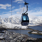 A view of Queenstown, New Zealand with the Skyline Gondola and the snow covered Remarkables mountain range providing a stunning backdrop after winter snowfalls..Queenstown is nestled on the shores of the crystal clear waters of Lake Wakatipu in the Central Otago region of the South Island of New Zealand..Queenstown is New Zealand's premier tourist destination providing an abundance of year round outdoor activities for both young and old. Queenstown, Central Otago, South Island, New Zealand. 10th July 2011. Photo Tim Clayton..