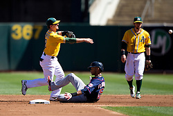 OAKLAND, CA - SEPTEMBER 22: Jed Lowrie #8 of the Oakland Athletics throws to first base to complete a double play over Pedro Florimon #25 of the Minnesota Twins during the second inning at O.co Coliseum on September 22, 2013 in Oakland, California. The Oakland Athletics defeated the Minnesota Twins 11-7 as they clinched the American League West Division. (Photo by Jason O. Watson/Getty Images) *** Local Caption *** Jed Lowrie; Pedro Florimon