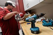 Equipment managers work in the Mal Moore Athletic Facility to get the University of Alabama football team ready for the trip to Baton Rouge to face LSU.  Michael Neese works on Nico Johnson's helmet in one of the equipment rooms.  Photo by Gary Cosby Jr.