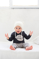 Baby Boy Sitting on Bed Wearing Knitted Hat
