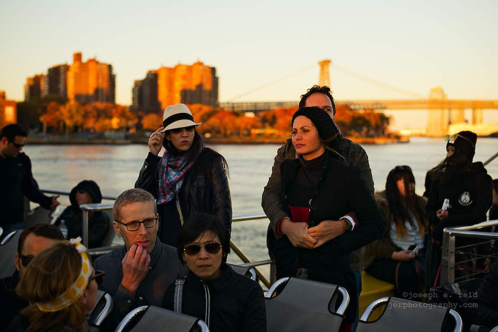People on ferry on East River on autumn afternoon, New York, NY, US