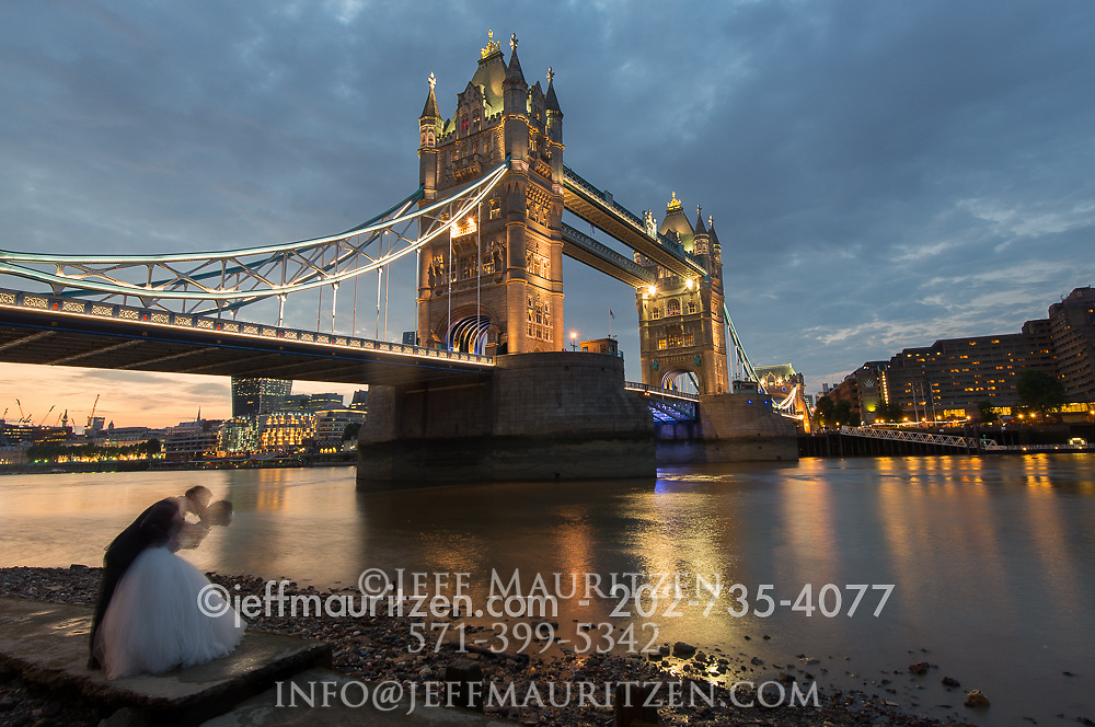 A bride and groom kiss in front of Tower Bridge at sunset.