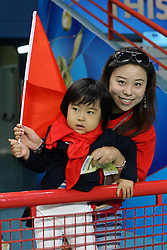 A young China fan follows the match with his mother