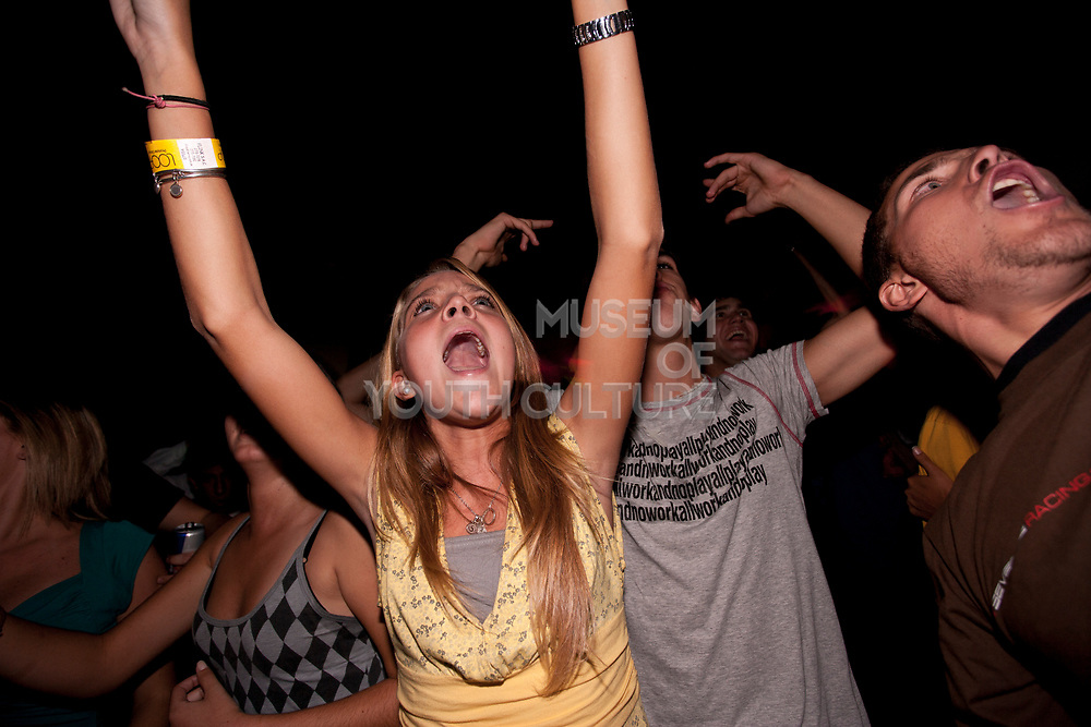 HAPPY PRETTY BLOND GIRL DANCING ARMS IN THE AR