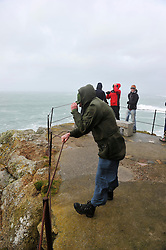 © Licensed to London News Pictures. Date 08/02/2014. Sennen Cove, UK. Members of the public cling on to railings to avoid being blown away by gale force winds as a storm hits the seafront at Sennen Cove at the Western tip of Cornwall. Photo credit : Mark Hemsworth/LNP