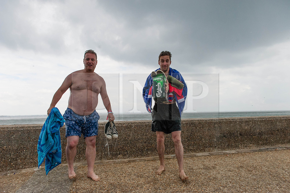 © Licensed to London News Pictures. 14/06/2014. Ryde, Isle of Wight, UK. A thundery downpour suddenly strikes Ryde causing sunbathers to grab their towels and run from the beach to cover.   Moments earlier it was hot & sunny. The UK is experiencing a period of hot sunny weather with temperatures over the weekend expected to reach 74 F (23 C).  Photo credit : Richard Isaac/LNP