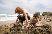 Two pre-teen boys playing in sand on beach
