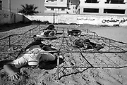 Palestinian boys crawl under a barb wire platform during HAMAS sponsored summer camp August 04, 2007 in Gaza City, Gaza. Kids from age 7 to 16 are given military style training 6 days a week at HAMAS camps like this across Gaza for 3 hours per day.