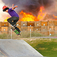 Brett Gomez attempts to land a trick as a large fire burns at the Yuma Mesa Fruit Growers Association, located at 2240 S. Pacific Ave, just East of the Kennedy Skate Park on Friday evening. A stack of cardboard and wooden crates stored at the business went up in flames sending a large plume of black smoke into the air that could be seen throughout the city.