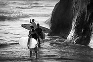 Group of male surfers carrying surfboards heading out.
