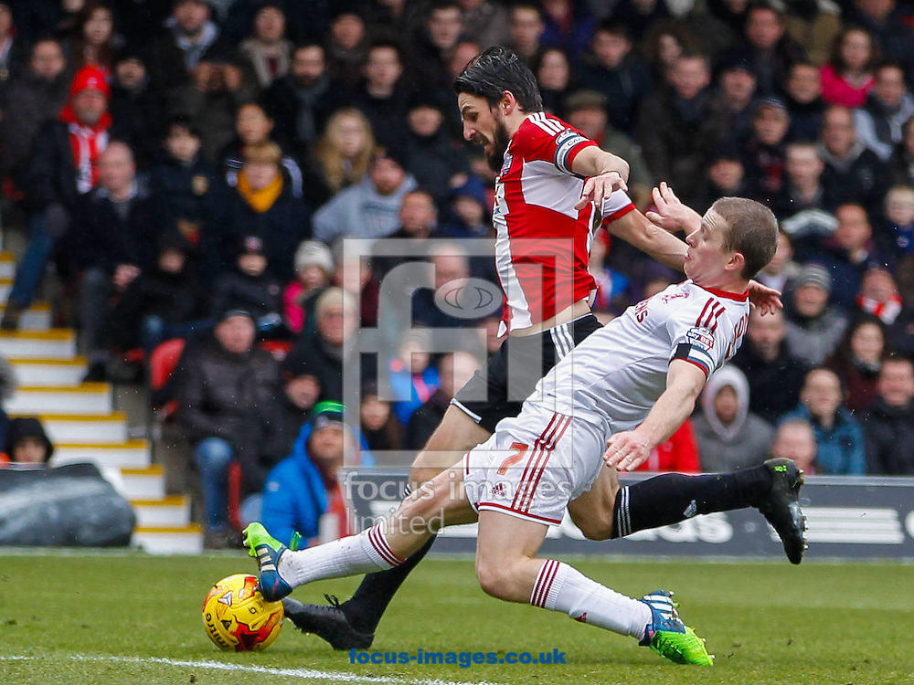 Jonathan Douglas of Brentford is tackled by Grant Leadbitter of Middlesbrough during the Sky Bet Championship match between Brentford and Middlesbrough at Griffin Park, London<br /> Picture by Mark D Fuller/Focus Images Ltd +44 7774 216216<br /> 31/01/2015