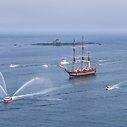 The Oliver Hazard Perry, escorted by the Portsmouth Fire Boat and other area vessels, enters the Piscataqua River near Kittery, ME and New Castle, NH during the Parade of Sail, August 10, 2016. Wood Island Life Saving Station and Whaleback Light are in the background.