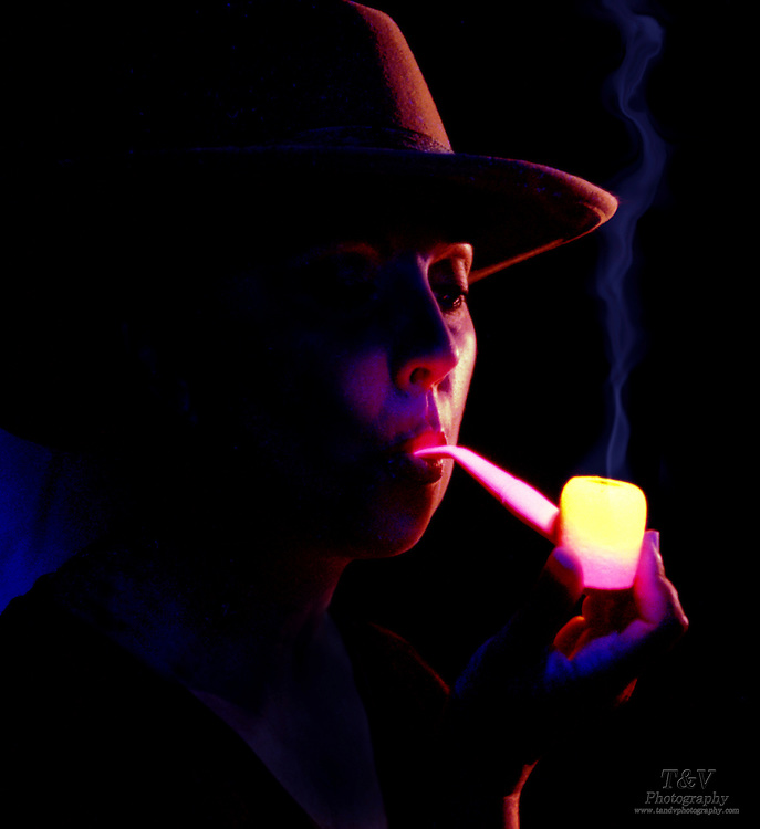 Woman with glowing corn cob pipe.Black light