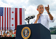 U.S. President Barack Obama loosens his tie in the heat before he delivers remarks on the economy at the Georgetown Waterfront Park in Washington.