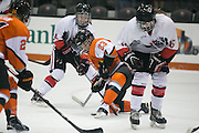 RIT Senior Captain Lindsay Grigg tries to keep the puck away from defenders from Pursuit of Excellence, a junior team from British Columbia, during an exhibition game at RIT's Gene Polisseni Center on Monday, September 29, 2014.