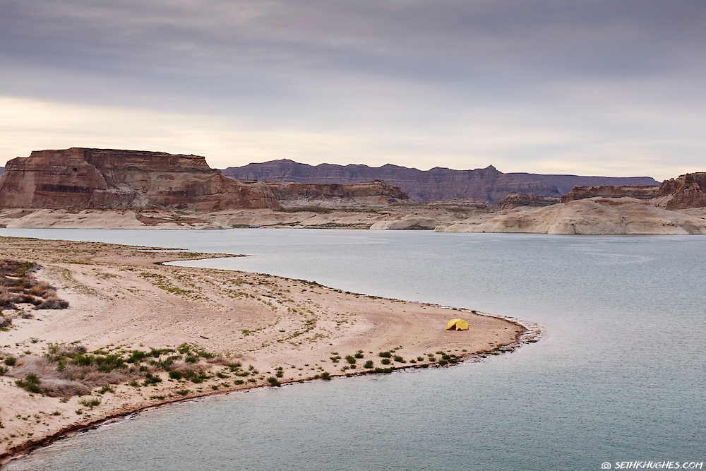 A solitary lakeside camping spot with a single tent surrounded by vast wilderness at Lake Powell, Utah.