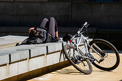 Saint Pauls Place a cyclist lays in the sun outside Sheffield Winter Gardenswhile some Areas of Sheffield city centre virtually deserted of people during the UK's  Social distancing and emergency lockdown measures which were announced Monday the 23rd April <br /> <br /> 24 April 2020<br /> <br /> www.pauldaviddrabble.co.uk<br /> All Images Copyright Paul David Drabble - <br /> All rights Reserved - <br /> Moral Rights Asserted -