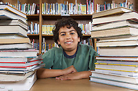 School boy sitting at desk with books in library, portrait
