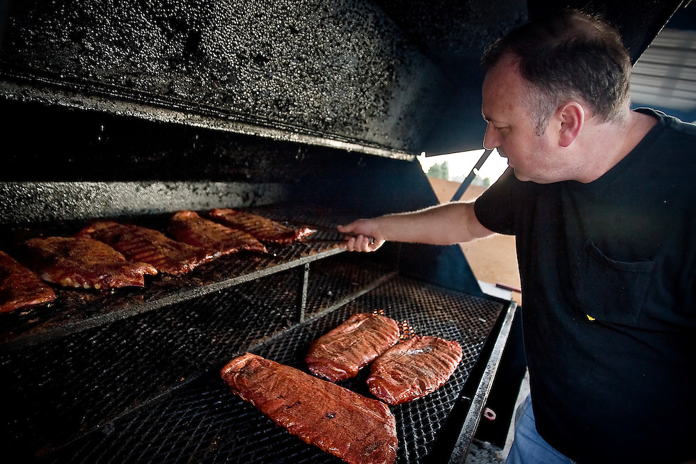 JEROME A. POLLOS/Press..Chris Clopton, co-owner of Porky G's Southern Style BBQ & Catering, tends to racks of ribs cooking in the smoker outside of their business on Dalton Avenue in Coeur d'Alene.