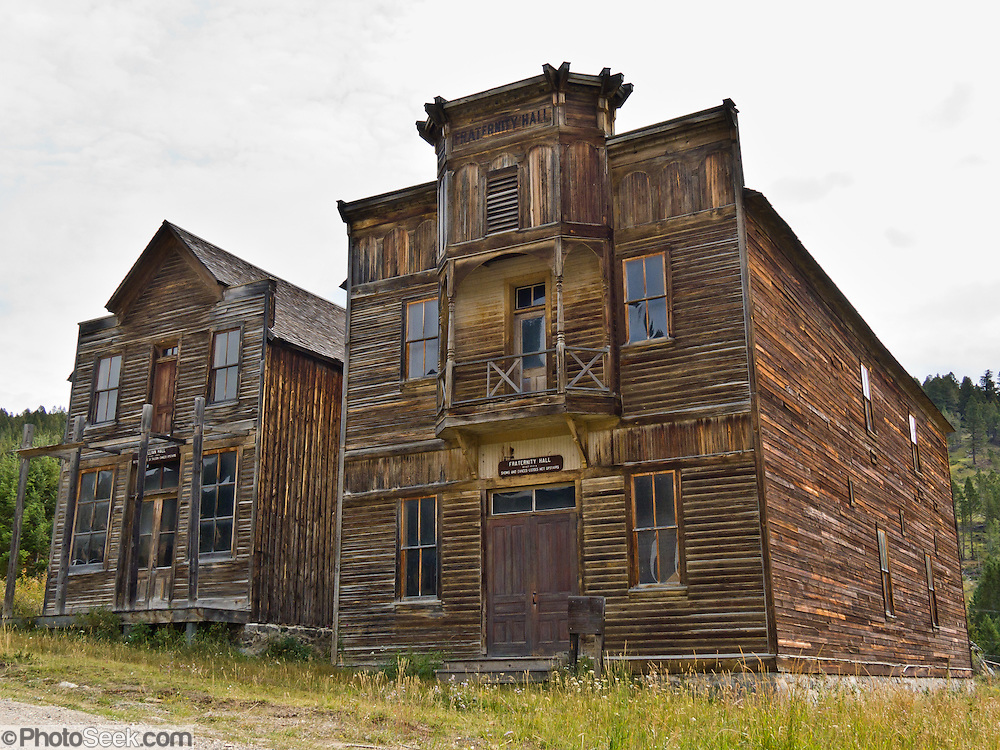 Two original buildings, outstanding examples of American frontier architecture, are preserved and open to the public as Elkhorn State Park (managed by the Montana Department of Fish, Wildlife, and Parks; and recorded in the Historic American Buildings Survey). Gillian Hall (left) was built in the 1880s and served as a store, saloon, and dance hall. Fraternity Hall (right), was built in the 1890s for shows, dances, and lodge meetings. The silver, gold and lead mines at Elkhorn began booming in 1875, then declined in 1892 as silver prices dropped. A few miners still work the Elkhorn mines and live in private homes near these historic State Park buildings within Beaverhead-Deerlodge National Forest. Directions: I-15 at Boulder exit, 7 miles south on Montana 69, then 11 miles north on county graveled road. (Lat 46.275,  Lng  -111.946)