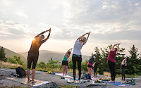 Kate Criscone from Body Design by Joy leads her group in sun salutations during sunrise yoga class from the top of Piper Mountain on Saturday morning.  (Karen Bobotas/for the Laconia Daily Sun)