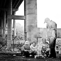 "CHONGQING - DEC 19, 2010: A family hanging out by the fire under one of the many concrete pilons holding up new built highways and interchanges in the city. ""Smooth Chongqing"" is one of the 5 slogans of the ""Wu ge Chongqing"", the governmental publicity for the Municipality."