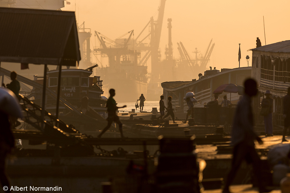 Busy port with workers at sunrise, Yangon
