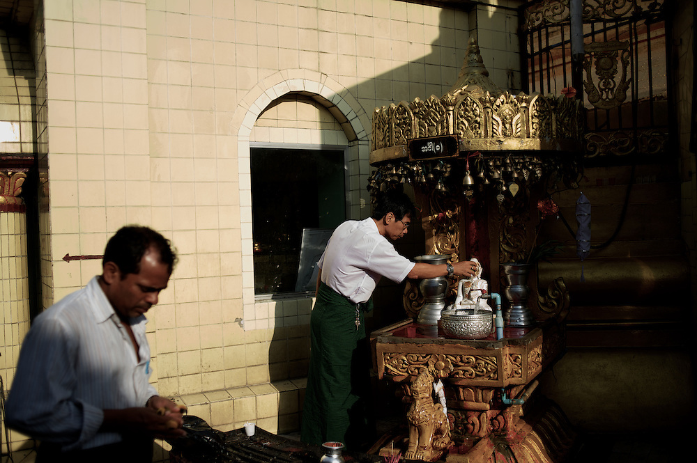 May 09, 2013 - Yangon, Myanmar: A devotee performs a ritual of water offer to a religious statue in a shrine at Sule Pagoda in central Yangon. (Paulo Nunes dos Santos/Polaris)