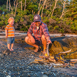 A man and his young son enjoy a camp fire on East Gosling Island in Casco Bay, Harpswell, Maine.