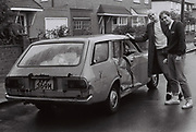 Teenagers standing by damaged car, London, UK, 1983