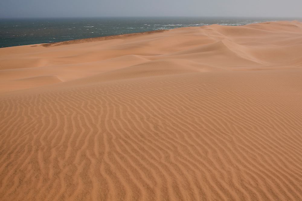 Dramatic contrast between the dessert dunes and the sea coast, in Namibia.