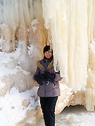 A beautiful woman poses behind an ice stalactite at the Apostle Island Ice Caves, Makwike Bay, near Bayfield, Wisconsin, on a cold February day.