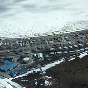 Shishmaref, Alaska, an Inupiat community of about 600 people near the Bering Strait, is seen from the air. The residents of Shishmaref voted to relocate because their island is steadily disappearing because of erosion and flooding due to climate change. Only one quarter mile wide and two and half miles long, Shishmaref has been  grappling with rising sea levels that have eroded more than 200 feet of the village, since 1969, according to a relocation study published in February. Climate change has resulted in a reduction in the sea ice which buffers Shishmaref from storm surges. At the same time, the permafrost that the village is built on has also begun to melt, making the shore even more vulnerable to erosion. The Inupiat rely heavily on a subsistence lifestyle, hunting and gathering much of their food. Shishmaref is one of at least 31 Alaska Native villages under imminent threat due to climate change, according to a 2009 report from the Government Accountability Office.