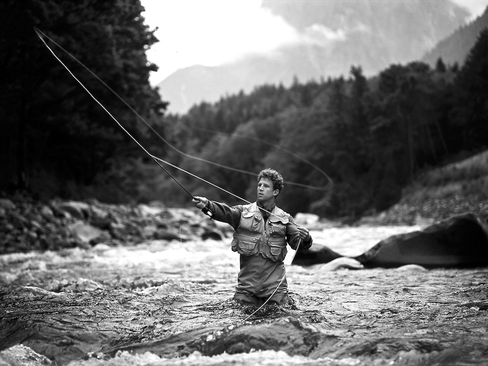 Fly fisherman casts line while wading in the middle of the Skykomish River in Washington State, USA, North America.  Lifestyle Photographer Robert Randall