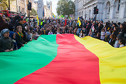 London, October 11th 2014. Thousands of protesters from the UK's Kurdish community demonstrate in London against the delay in assisting the people of the Syrian city of Kobane in their fight against ISIS. They also accuse Turkey, with whom the Kurds have had a long-running insurgency of siding with the Islamic State by doing nothing to help Kurds in Kobane. PICTURED: A Huge flag in the Kurdish colours was carried by women and children on the march.