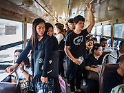 15 OCTOBER 2016 - BANGKOK, THAILAND: People wearing black mourning for Bhumibol Adulyadej, the King of Thailand ride a free city bus to the Grand Palace. The city and private businesses are setting up shuttles to take people to Grand Palace so they can mourn the King. King Bhumibol Adulyadej died Oct. 13, 2016. He was 88. His death comes after a period of failing health. With the king's death, the world's longest-reigning monarch is Queen Elizabeth II, who ascended to the British throne in 1952. Bhumibol Adulyadej, was born in Cambridge, MA, on 5 December 1927. He was the ninth monarch of Thailand from the Chakri Dynasty and is known as Rama IX. He became King on June 9, 1946 and served as King of Thailand for 70 years, 126 days. He was, at the time of his death, the world's longest-serving head of state and the longest-reigning monarch in Thai history.      PHOTO BY JACK KURTZ