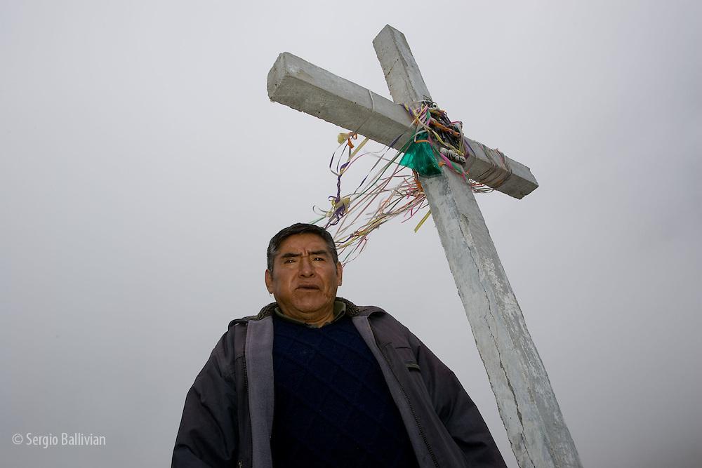 "A Kallawaya spiritual man performs a ""ch'alla"" to appease the spirits at the ""Cumbre"" pass near La Paz, Bolivia"