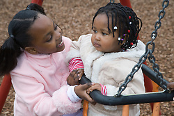 Two sisters playing on a swing in the playground,