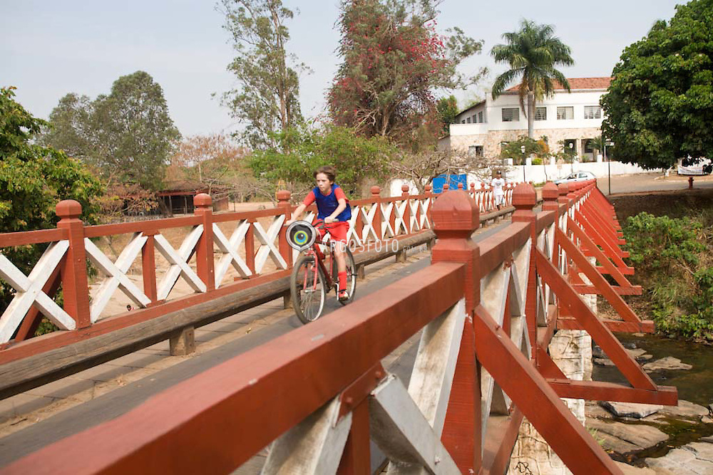 Menino atravessando a Ponte de Madeira na sua bicicleta, na cidade  historica de Pirenopolis, em Goias. / Boy crossing the Bridge of Wood in his bike. Pirenopolis is a town located in the Brazilian state of Goias. It is well-known for its waterfalls and colonial architecture