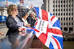 © Licensed to London News Pictures. 15/06/2016. London, UK. A woman flies a Union Jack Flag on London Bridge as the pro-Brexit campaign 'Fishermen for Leave' sail a flotilla of over 30 vessels up the Thames. The flotilla, including UKIP leader Nigel Farage, caused traffic issues in central London, as vessels travelled up the Thames for high tide and to coincide with the last Prime Minister's Questions before the EU referendum takes place on 23 June. Photo credit : Tom Nicholson/LNP