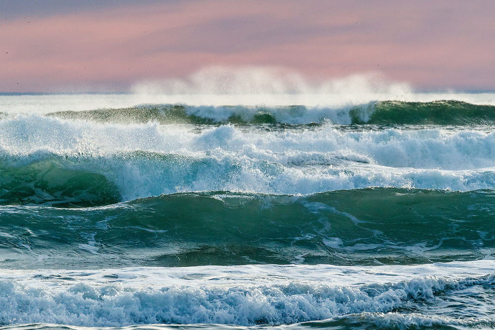 Pacific Ocean waves breaking at Chapman Beach in pastel sunset, near town of Cannon Beach, Oregon, USA.