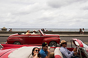 Locals and tourists stroll along one of the main avenues by the sea  of Havana,Cuba.