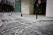 Incongruous modern City of London corporate architecture and older cycling road markings.