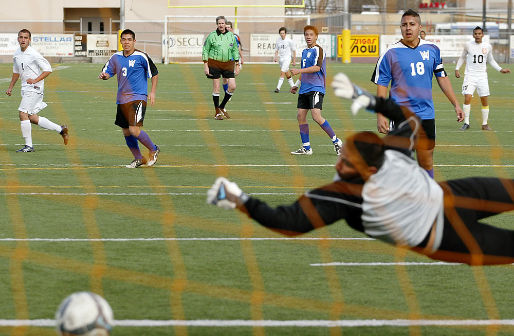 Players from Kennewick, in white, and Walla Walla watch as Walla Walla goalie Tomas Gonzalez just misses as he dives for a shot on goal by Kennewick's Geovanny Vasquez (not pictured) during Walla Walla's 2-1 win at Lampson Stadium in Kennewick. The shot went wide right, barely missing the goal.