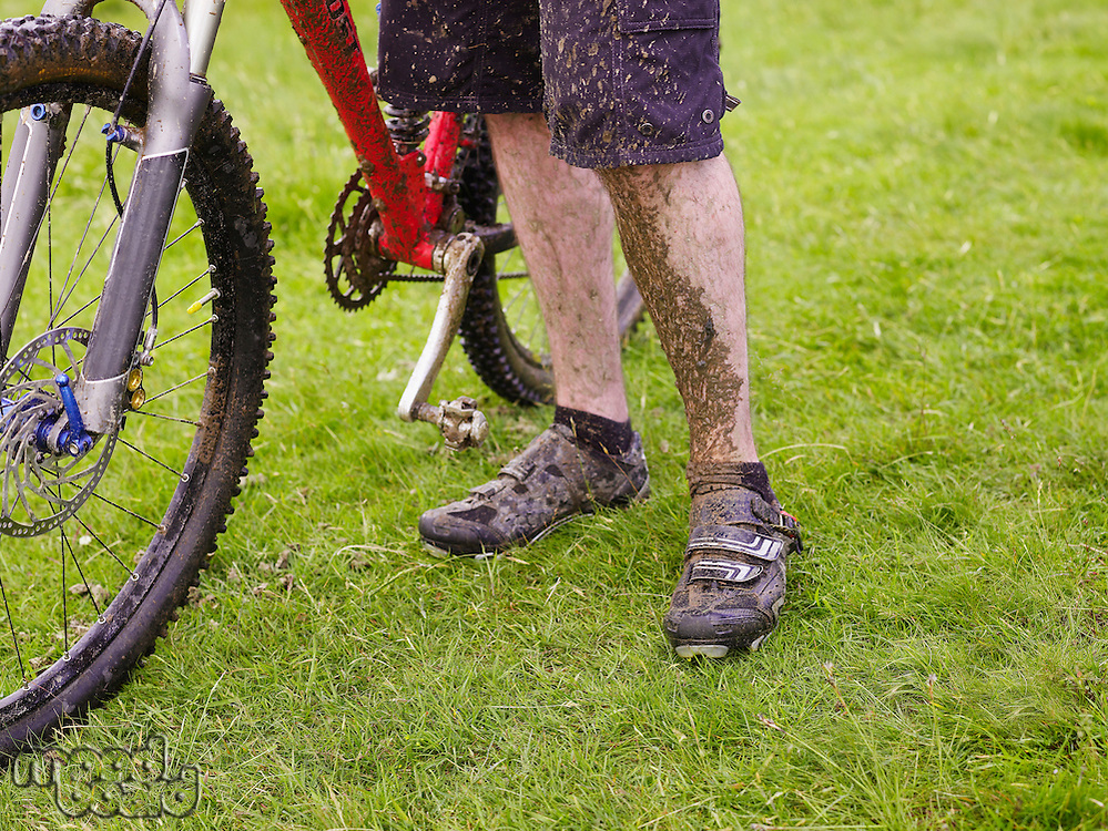 Muddy cyclist with bike outdoors