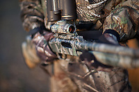 DETAIL OF A MOSSBERG DEER HUNTING SHOTGUN SLUG GUN WITH A HOLOGRAPHIC SCOPE
