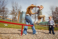 JEROME A. POLLOS/Press..Payson Irwin, 3, jumps from a balance beam with the assistance of his mother Holly while his brother Cooper waits his turn Tuesday at McEuen Park in Coeur d'Alene. Irwin, his mother Holly and twin brother Payson, enjoyed a picnic in the park and an afternoon of playing in the mild weather.